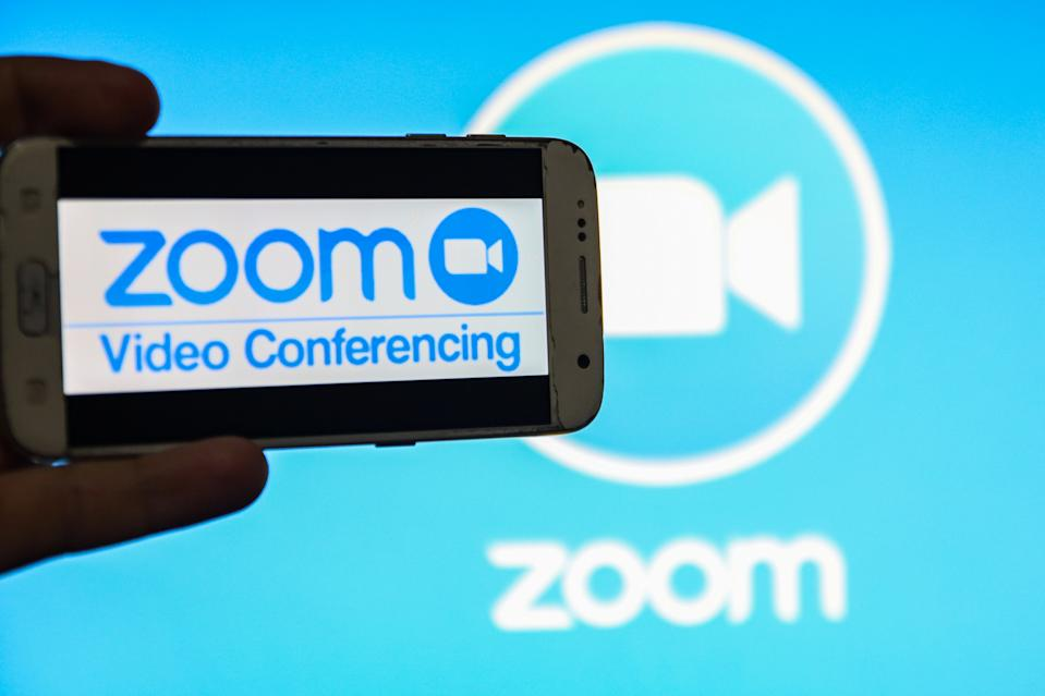 ZOOM Video Communications logo displayed on a phone screen, thumbnails of the application, smartphone and keyboard are seen in this multiple exposure illustration. Zoom is an American communications technology company headquartered in San Jose, California. It provides videotelephony and online chat services through a cloud-based peer-to-peer software platform and is used for teleconferencing, telecommuting, distance education, and social relations. Zoom App and communication became very popular during the Covid-19, Coronavirus pandemic quarantine lockdown and social distancing as people started massively distant video telecommunication. Thessaloniki, Greece April 24, 2020 (Photo by Nicolas Economou/NurPhoto via Getty Images)