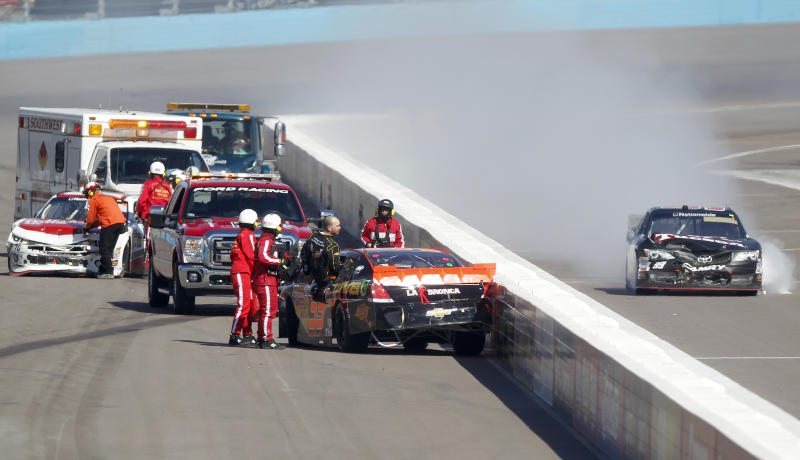 Jamie Dick, front, climbs out of his car following a collision with Johanna Long, left rear, and Alex Bowman, right, on the front stretch on the second lap of the NASCAR Nationwide Series auto race Saturday, March 2, 2013, at Phoenix International Raceway in Avondale, Ariz. (AP Photo/Paul Connors)