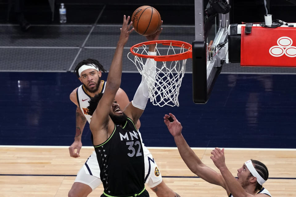 Minnesota Timberwolves' Karl-Anthony Towns (32) reaches for a rebound as Denver Nuggets' JaVale McGee, left, and Aaron Gordon watch during the first half of an NBA basketball game Thursday, May 13, 2021, in Minneapolis. (AP Photo/Jim Mone)
