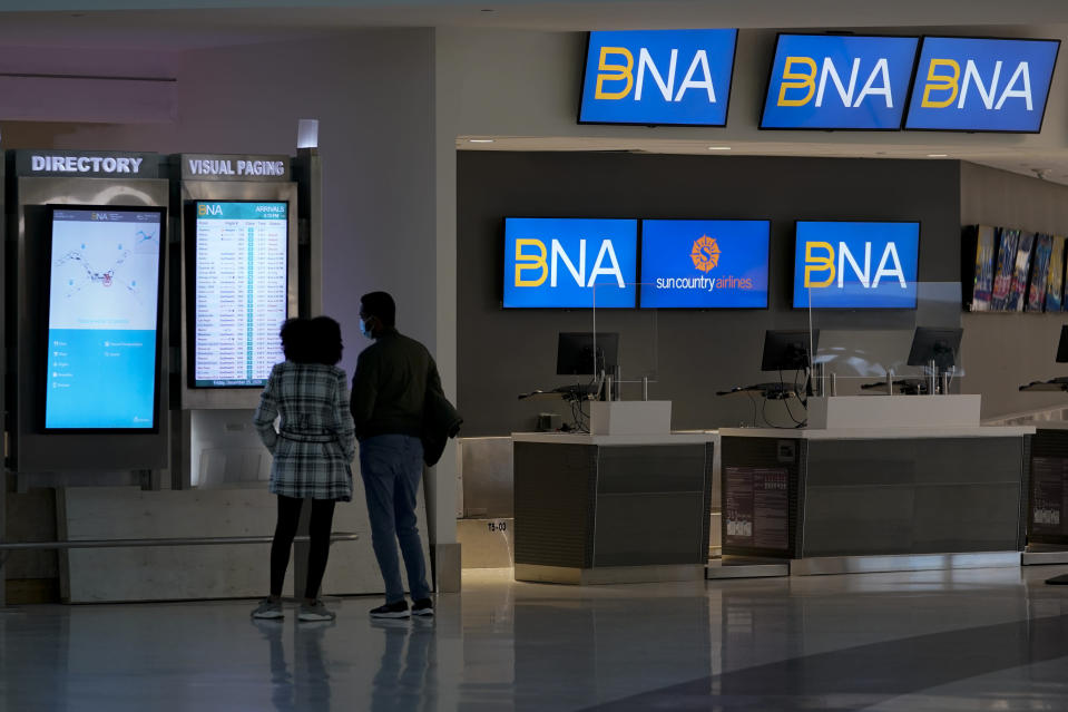 A couple checks flight status at Nashville international Airport Friday, Dec. 25, 2020 in Nashville. Tenn. Flights were impacted because of telecommunications issues associated with explosion in downtown. (AP Photo/Mark Humphrey)
