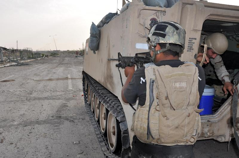 Iraqi government forces stand guard next to a tank on June 24, 2014 in the western city of Ramadi