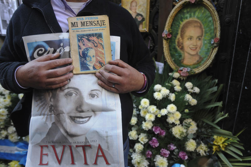 """A man displays pictures Argentina's late former first lady Maria Eva Duarte de Peron, better known as """"Evita,"""" as he stands by her tomb in Buenos Aires, Argentina, Thursday, July 26, 2012. Argentines commemorate the 60th anniversary of the death of their most famous first lady on Thursday. Evita died of cancer on July 26, 1952 at the age of 33. (AP Photo/Sergio Goya)"""
