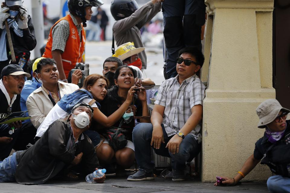 Anti-government protesters and other civilians take cover as shots are fired during clashes near the Government House in Bangkok February 18, 2014. A Thai police officer was killed and dozens of police and anti-government protesters were wounded in gun battles and clashes in Bangkok on Tuesday, officials and witnesses said. REUTERS/Damir Sagolj (THAILAND - Tags: POLITICS CIVIL UNREST TPX IMAGES OF THE DAY)