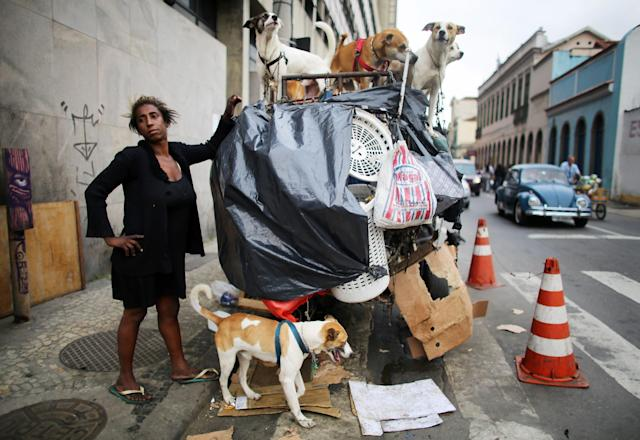 RIO DE JANEIRO, BRAZIL - OCTOBER 30: Rosana Moses stands with the family of 16 dogs she cares for in the port district as revitalization efforts continue on October 30, 2013 in Rio de Janeiro, Brazil. Moses lives on the streets and relies on donations to help care for the dogs. Ahead of the Rio 2016 Olympic Games, Rio has started a multibillion dollar urban renewal program of its port district which includes a double decker waterfront freeway being torn down to be replaced by tunnels, repaved roads, a tram network and other infrastructure improvements in the area. The 'Porto Maravilha' project is also expected to displace around 1,000 local residents. (Photo by Mario Tama/Getty Images)