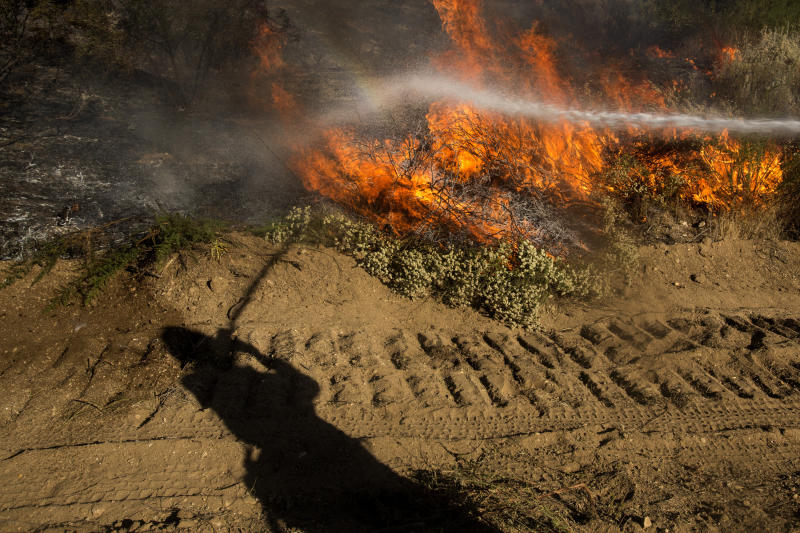 A firefighter casts a shadow next to a brush fire, as crews work against the Apple Fire near Banning, Calif., Sunday, Aug. 2, 2020. (AP Photo/Ringo H.W. Chiu)