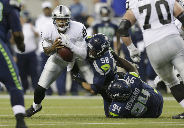Under pressure form Seattle Seahawks' Ty Powell (58) and Jaye Howard (94), Oakland Raiders quarterback Terrelle Pryor, left, fumbles the football, but later recovered it, in the first half of an NFL preseason football game on Thursday, Aug. 29, 2013, in Seattle. (AP Photo/Stephen Brashear)
