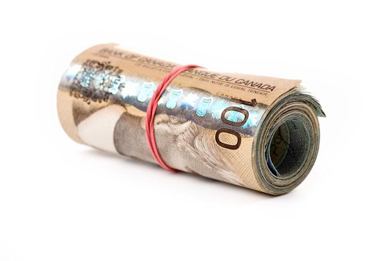 File photo of Canadian money wound up in a roll. The Parliamentary Budget Office estimates a six-month basic income program would cost at least $47.5 billion. (Photo: Devonyu via Getty Images)