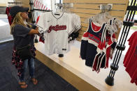 Julie Howe looks at Cleveland Indians apparel in the Indians team shop before a baseball game, Monday, Sept. 27, 2021, in Cleveland. Cleveland will play its final home game against the Kansas City Royals as the Indians, the team's nickname since 1915. The club will be called the Cleveland Guardians next season. (AP Photo/Tony Dejak)