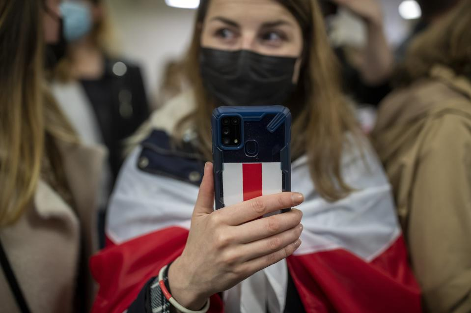 A woman covered herself by an old Belarusian national flag holds a smart phone with a sticker in colors of an old Belarusian national flag as she waits to see passengers of the Ryanair plane with registration number SP-RSM, carrying opposition figure Raman Pratasevich which was traveling from Athens to Vilnius and was diverted to Minsk after a bomb threat, after its landing at the International Airport outside Vilnius, Lithuania, Sunday, May 23, 2021. The presidential press service said President Alexander Lukashenko personally ordered that a MiG-29 fighter jet accompany the Ryanair plane carrying opposition figure Raman Pratasevich and traveling from Athens, Greece, to Vilnius, Lithuania to the airport in the capital Minsk. (AP Photo/Mindaugas Kulbis)