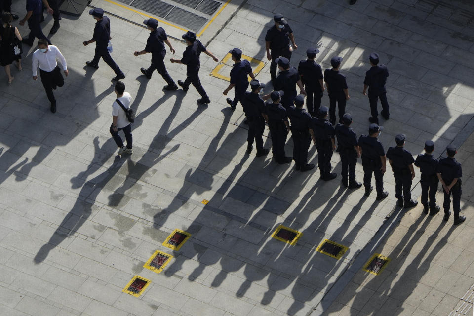 Security personnel march to duty outside the Evergrande headquarters in Shenzhen, China, Friday, Sept. 24, 2021. Things appeared quiet at the headquarters of the heavily indebted Chinese real estate developer Evergrande, one day after the day it had promised to pay interest due to bondholders in China. (AP Photo/Ng Han Guan)