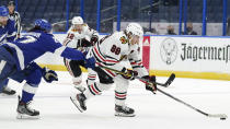 Chicago Blackhawks right wing Patrick Kane (88) breaks past Tampa Bay Lightning defenseman Ryan McDonagh (27) during the first period of an NHL hockey game Friday, Jan. 15, 2021, in Tampa, Fla. (AP Photo/Chris O'Meara)