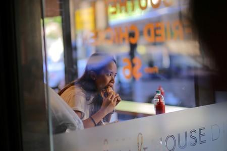 FILE PHOTO: A woman can be seen through the window of a fast-food restaurant eating a burger in Sydney, Australia