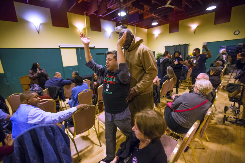 A protester is led out after grabbing the microphone during a gathering of community leaders to discuss Mayor Pete Buttigieg's work Wednesday, Dec. 4, 2019 at the Charles Martin Center in South Bend, Indiana. (Michael Caterina/South Bend Tribune via AP)