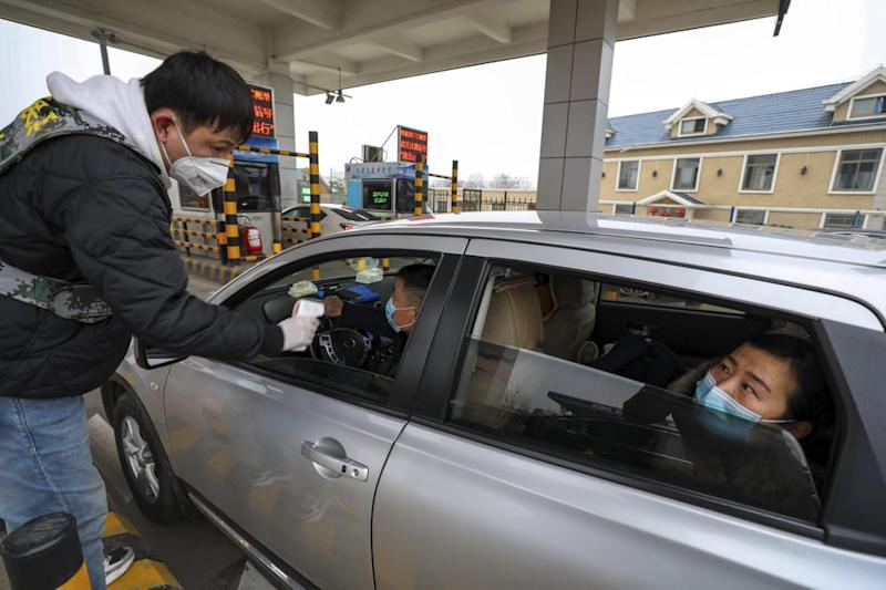 A militia member uses a thermometer gun to take a driver's temperature at a Wuhan toll gate amid the coronavirus outbreak.