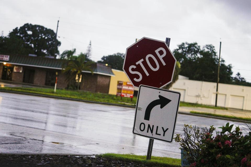 A couple of signs hang loose on their post after Hurricane Elsa moved over the Tampa Bay Area, Wednesday, July 7, 2021 in Pinellas Park, Fla. The Tampa Bay area was spared major damage as Elsa stayed off shore as it passed by. (Martha Asencio-Rhine/Tampa Bay Times via AP)