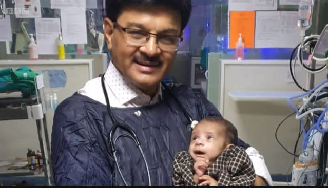 Indian doctor Ravi Khanna holding the baby girl who was found buried alive.
