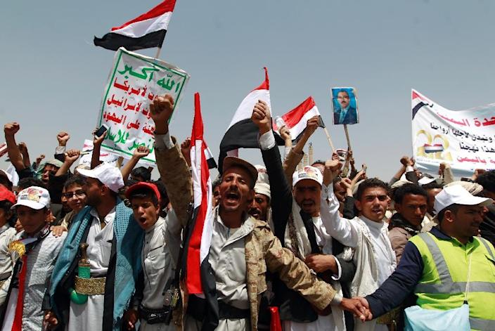 Yemenis shout slogans and wave national flags as they take part in celebrations marking the 26th anniversary of Yemen's 1990 reunification in the capital Sanaa (AFP Photo/Mohammed Huwais)
