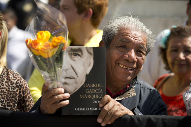 A well-wisher holds flowers and an autobiography of Colombian Nobel Literature laureate Gabriel Garcia Marquez, as he waits outside the Palace of Fine Arts to pay his respect to the beloved author, in Mexico City, Monday, April 21, 2014. Garcia Marquez died Thursday April 17, 2014 at his home in Mexico City. The author's magical realist novels and short stories exposed tens of millions of readers to Latin America's passion, superstition, violence and inequality. (AP Photo/Rebecca Blackwell)