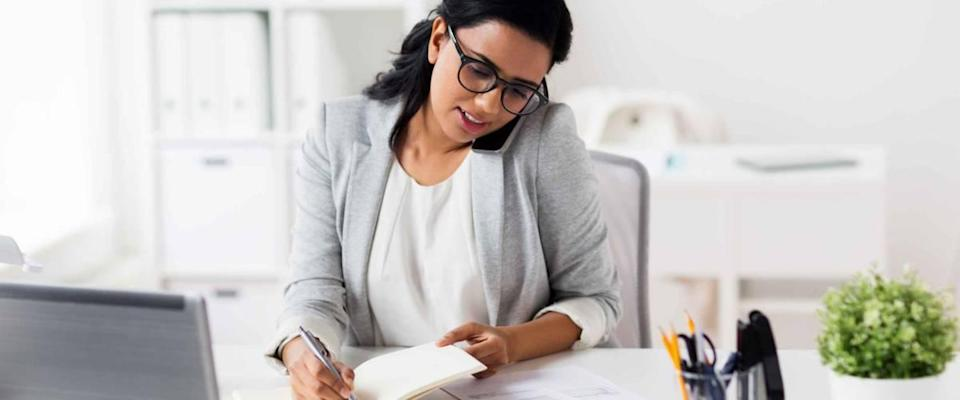 happy businesswoman or secretary with notebook calling on smartphone at office