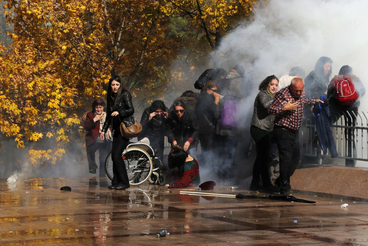 REFILE ADDING CAPTION INFORMATION   Protesters help a handicapped protester, who fell from her wheelchair after tear gas was shot towards them, during a demonstration in front of a courthouse in Ankara October 28, 2013. Turkish police fired water cannon and teargas on Monday to break up a protest by around 2,000 people outside the court over the handling of the trial of a policeman accused of killing a demonstrator earlier this year. Officer Ahmet Sahbaz is accused of killing Ethem Sarisuluk, shot dead in June during a wave of nationwide anti-government demonstrations set off by a tough police response to a protest over the redevelopment of a park in Istanbul. REUTERS/Umit Bektas (TURKEY - Tags: POLITICS CIVIL UNREST CRIME LAW TPX IMAGES OF THE DAY)