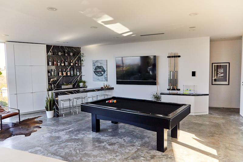 """During the remodel, the space that was being used as the living room became Huston's entertainment room, complete with a pool table from his previous home that he re-covered in black felt, and a new black marble bar featuring slabs he hand-selected. """"I haven't had an official party here, but it's definitely a good room for entertaining,"""" says the billiards enthusiast."""