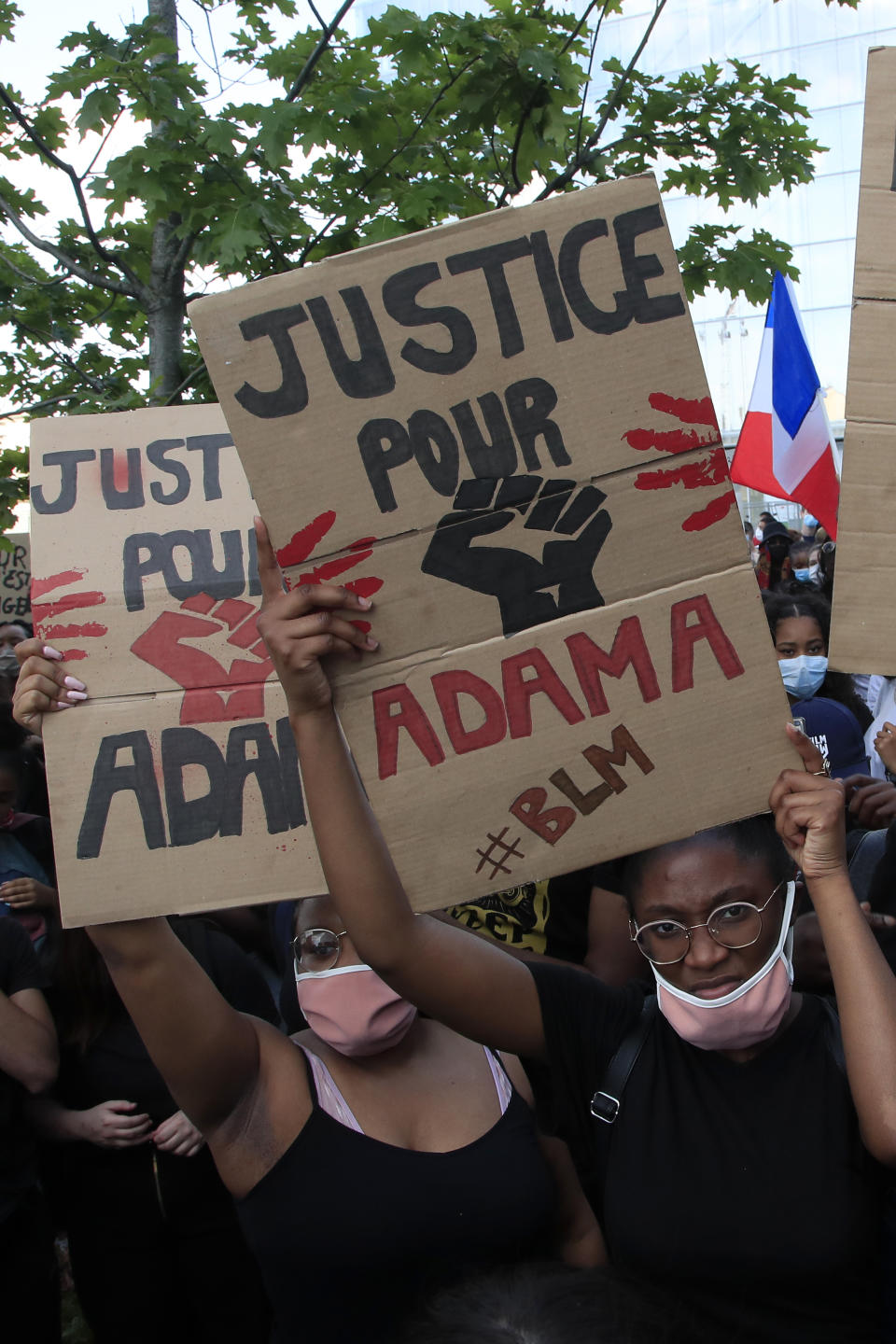 """Protesters shows posters reading """"Justice for Adama"""" outside the courthouse Tuesday, June 2, 2020 in Paris. Thousands of people defied a police ban and converged on the main Paris courthouse for a demonstration to show solidarity with U.S. protesters and denounce the death of a black man in French police custody. The demonstration was organized to honor Frenchman Adama Traore, who died shortly after his arrest in 2016, and in solidarity with Americans demonstrating against George Floyd's death. (AP Photo/Michel Euler)"""
