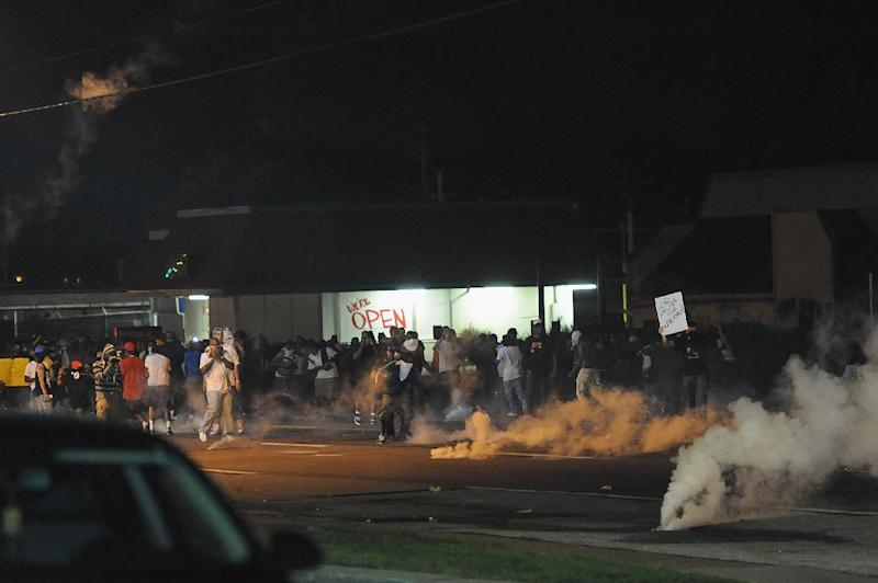 Protestors flee from tear gas being fired by law enforcement during a protest on West Florissant Road in Ferguson, Missouri on August 17, 2014 (AFP Photo/Michael B. Thomas)