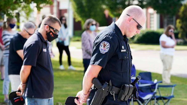 PHOTO: Officer Ben Hubbard, of the Collierville Police Department, and other residents pray during a vigil at Town Hall, Collierville, Tenn., Sept. 24, 2021. (Mark Humphrey/AP)
