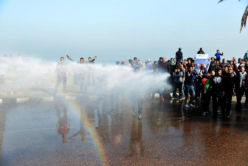 A rainbow forms as riot police use a water cannon to disperse a demonstration in Alexandria, Egypt, Monday, Dec. 2, 2013. Black clad riot police fired tear and chased dozens of rights activists and protesters who held a demonstration in the Mediterranean city demanding abolishing a new law that extensively restricted the right to hold a protest, imposing fines and jail terms on violators.(AP Photo/Heba Khamis)