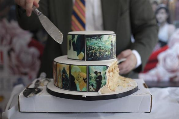 A man cuts cake for guests after the wedding of Jason Welker and Scott Everhart at a comic book retail shop in Manhattan, New York June 20, 2012.