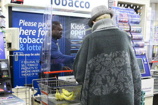 A cashier at a Tesco supermarket works behind a protective perspex barrier in Croydon, south London. Photo: Justin Tallis/AFP via Getty
