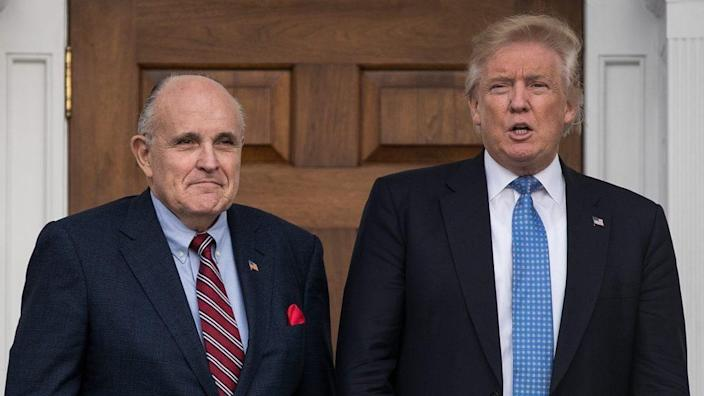 Shown just weeks after his 2016 election, then-President-elect Donald Trump (right) shares a moment with former New York City Mayor Rudy Giuliani before their meeting at Trump International Golf Club in New Jersey. (Photo by Drew Angerer/Getty Images)