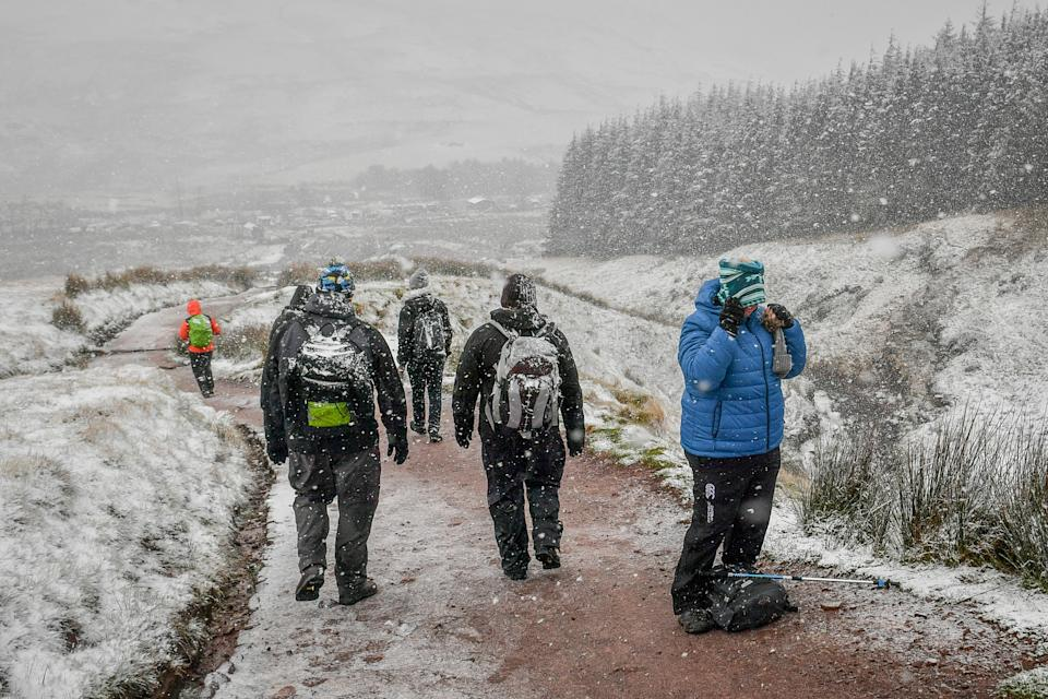 A woman pauses to pull on a snood as she hikes up Pen y Fan as snow falls on the Brecon Beacons National Park, Wales, as much of the UK experiences wintry weather on the first weekend of December, with warnings in place for ice and snow.