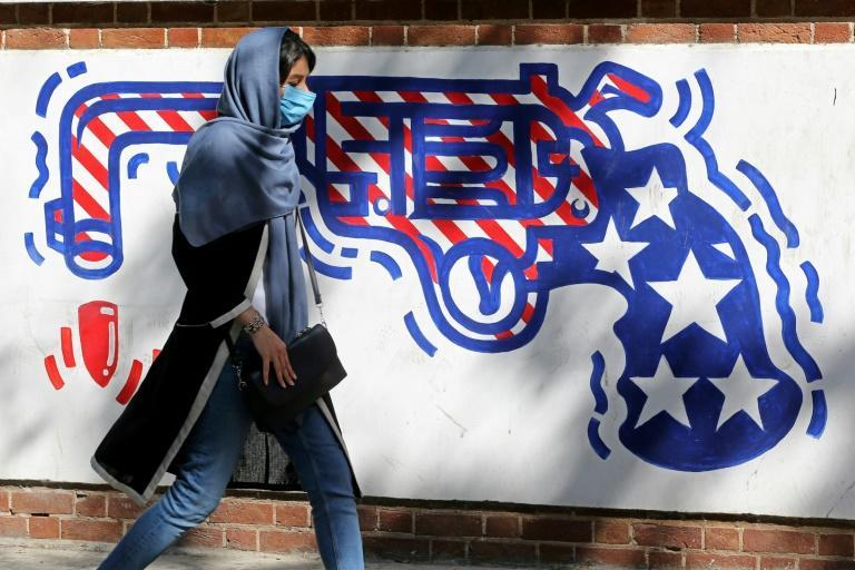 An Iranian woman walks past a mural painted on the outer walls of the former US embassy in Tehran on September 20, 2020