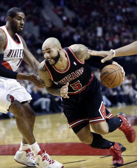 Chicago Bulls forward Carlos Boozer, right, drives against Portland Trail Blazers forward LaMarcus Aldridge during the first half of an NBA basketball game in Portland, Ore., Friday, Nov. 22, 2013. (AP Photo/Don Ryan)