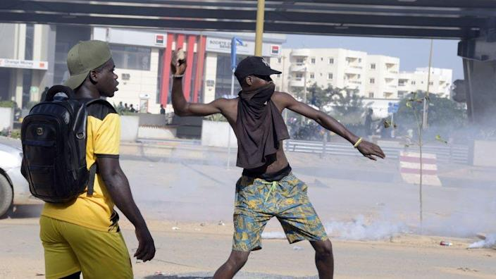 A protestor throws a rock during a demonstration of members of the Guinean opposition,