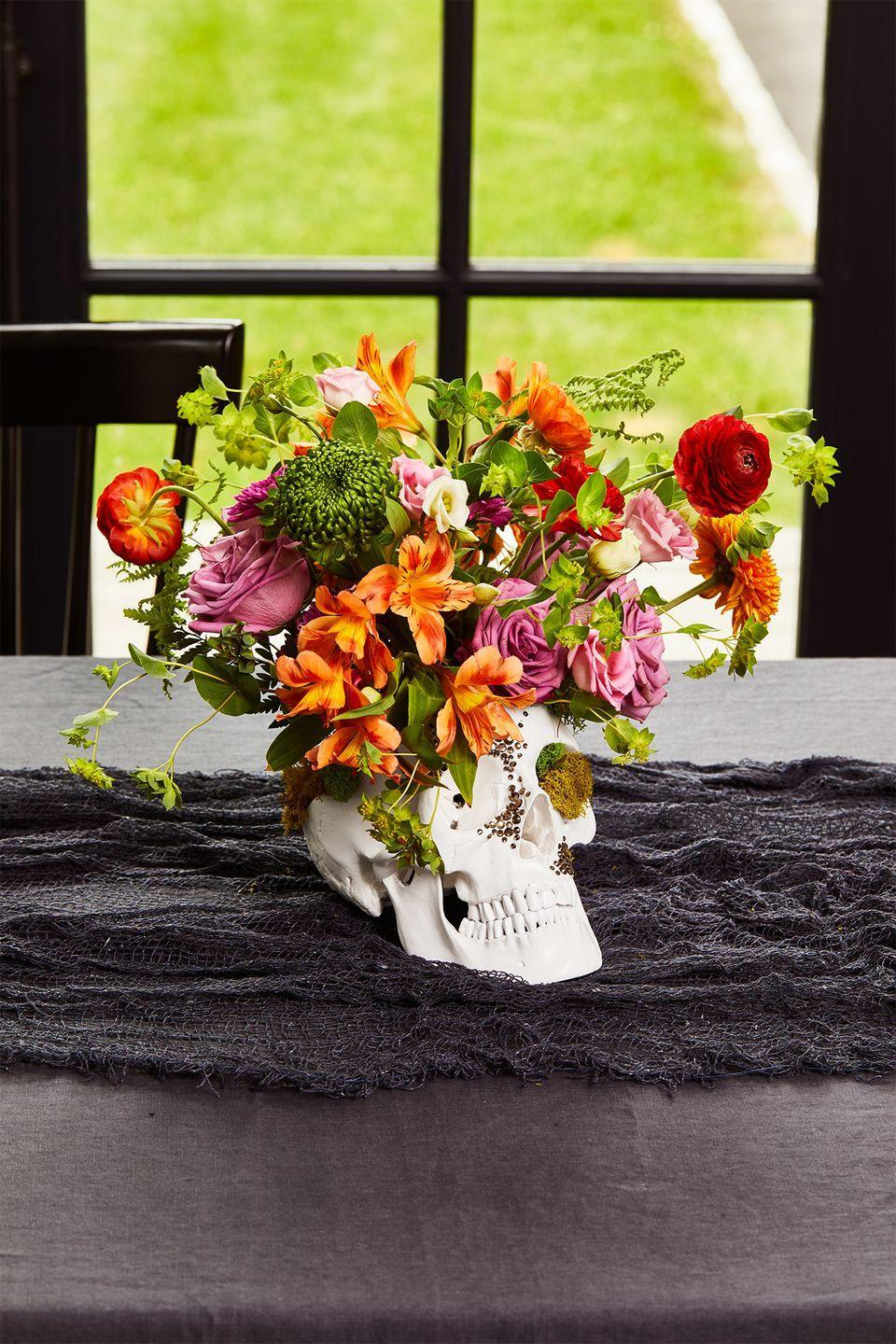 """<p>Channel Morticia Addams to create and add a gothic, otherwordly touch to your dining table with a skull centerpiece adorned with self-adhesive <a href=""""https://www.amazon.com/Rhinestone-Stickers-Nicpro-Self-Adhesive-Embellishments/dp/B0771MPKQD/ref=sr_1_3_sspa?tag=syn-yahoo-20&ascsubtag=%5Bartid%7C10055.g.33437890%5Bsrc%7Cyahoo-us"""" rel=""""nofollow noopener"""" target=""""_blank"""" data-ylk=""""slk:rhinestones"""" class=""""link rapid-noclick-resp"""">rhinestones</a>. Place a jar or cup inside a <a href=""""https://www.amazon.com/Wellden-Medical-Anatomical-Classic-3-part/dp/B0077B3L42/ref=sr_1_11?tag=syn-yahoo-20&ascsubtag=%5Bartid%7C10055.g.33437890%5Bsrc%7Cyahoo-us"""" rel=""""nofollow noopener"""" target=""""_blank"""" data-ylk=""""slk:faux skull"""" class=""""link rapid-noclick-resp"""">faux skull</a> with a removable top (you can use small rocks or gravel to help keep the cup in place). Then create a grid of tape on the rim of the jar to keep flower and greenery stems in place. Fill ⅔ with water and begin by arranging greenery and larger blooms in the grid, making sure to remove any leaves or extra stems that will sit below the water line. Finish with more delicate flowers.</p>"""