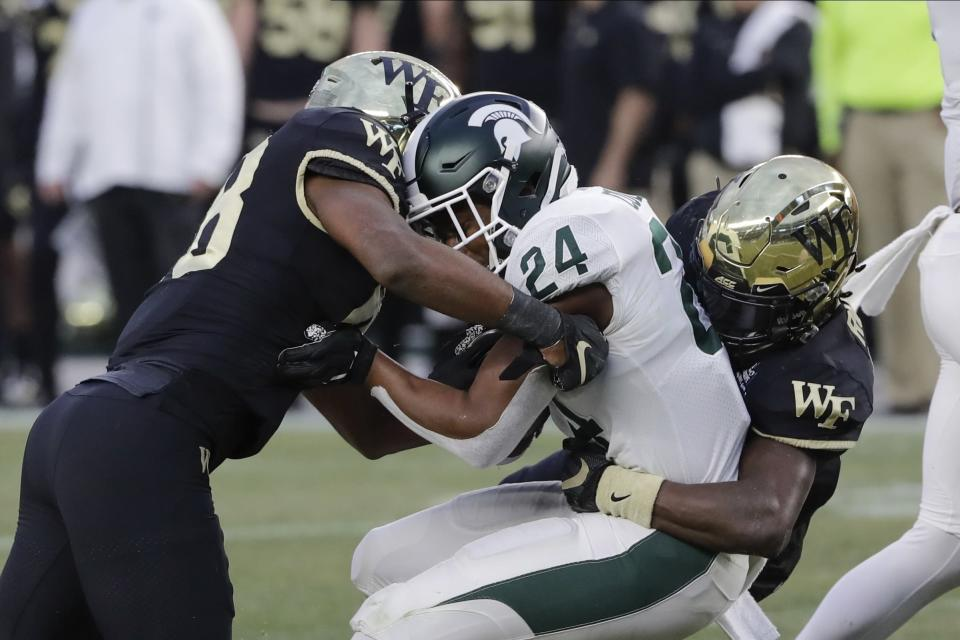 Wake Forest's Jack Connelly, left, and Trey Rucker, right, tackle Michigan State's Elijah Collins during the first half of the Pinstripe Bowl NCAA college football game Friday, Dec. 27, 2019, in New York. (AP Photo/Frank Franklin II)
