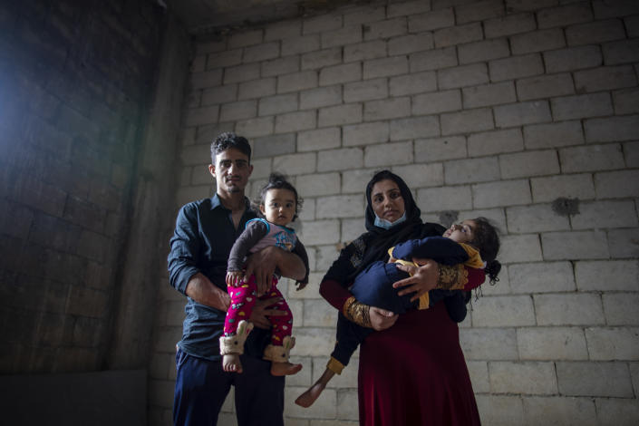 Syrian refugees Raed Mattar, 24, left, poses for a photograph with his wife Ayesha al-Abed, 21, and their daughters Rahaf, 6 years old, right, and Rayan, 18 months old, at an informal refugee camp, in the town of Rihaniyye in the northern city of Tripoli, Lebanon, Tuesday, April 13, 2021. For many Syrian refugee families in Lebanon, Ramadan comes as a hard life of displacement has gotten even harder after a pandemic year that deepened economic woes in their host country. (AP Photo/Hassan Ammar)
