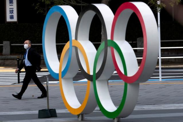 A man wearing a protective face mask, following an outbreak of the coronavirus disease (COVID-19), walks past walk past the Olympic rings in front of the Japan Olympics Museum in Tokyo