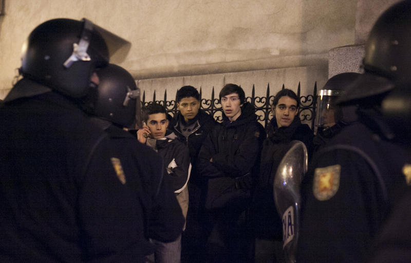 "Demonstrators are held by riot police officers following a protest in Madrid, Spain, Sunday, Feb. 24, 2013. Tens of thousands of people marched on Spain's parliament on Saturday to protest austerity measures, a demonstration that came on the 32nd anniversary of a failed attempt by the armed forces to overthrow the government. Protest groups joined forces under the slogan ""Citizens' Tide, 23F,"" referring to the Feb. 23, 1981, attack by the armed forces on the parliament. (AP Photo/Gabriel Pecot)"