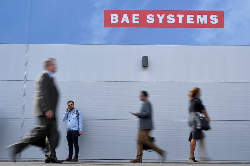 Trade visitors walk past an advertisement for BAE Systems at Farnborough International Airshow in Farnborough, Britain