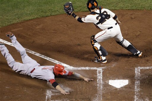 Cincinnati Reds' Joey Votto, left, slides into home to score on a single hit by Scott Rolen in the fourth inning as San Francisco Giants catcher Buster Posey, right, attempts to tag him during Game 2 of the National League division baseball series in San Francisco, Sunday, Oct. 7, 2012. (AP Photo/Marcio Jose Sanchez)