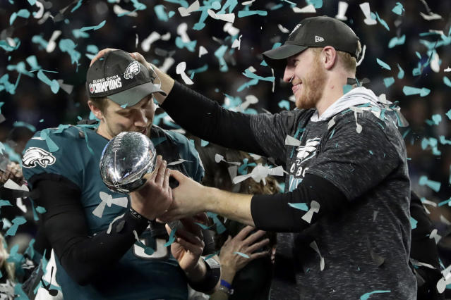 Eagles quarterback Carson Wentz (right) hands the Vincent Lombardi trophy to Nick Foles after the Super Bowl. (AP)