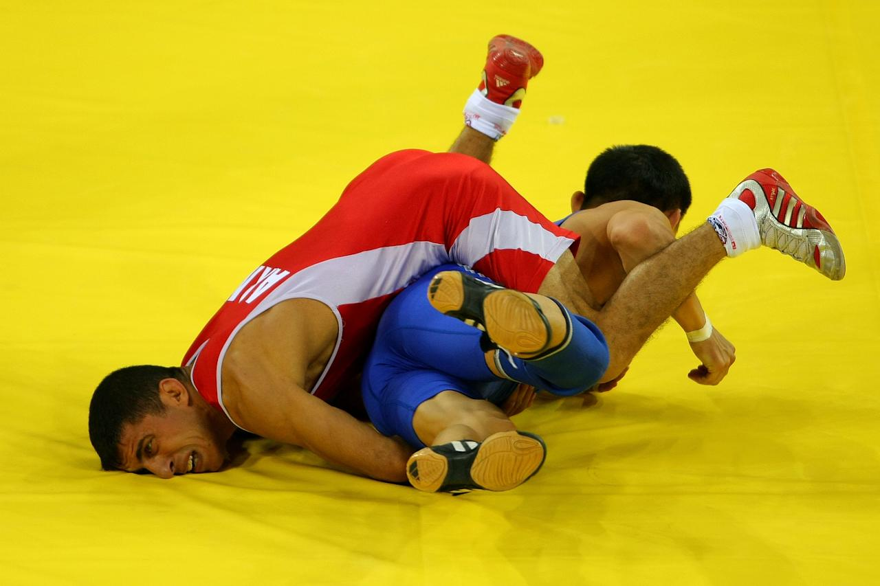 BEIJING - AUGUST 12:  Roman Amoyan (red) of Armenia competes against Asset Imanbayev of Kazakhstan in their Men's Greco-Roman 55 kg qualifying wrestling event during Day 4 of the Beijing 2008 Olympic Games at the China Agriculture University Gymnasiumon August 12, 2008 in Beijing, China.  (Photo by Stu Forster/Getty Images)