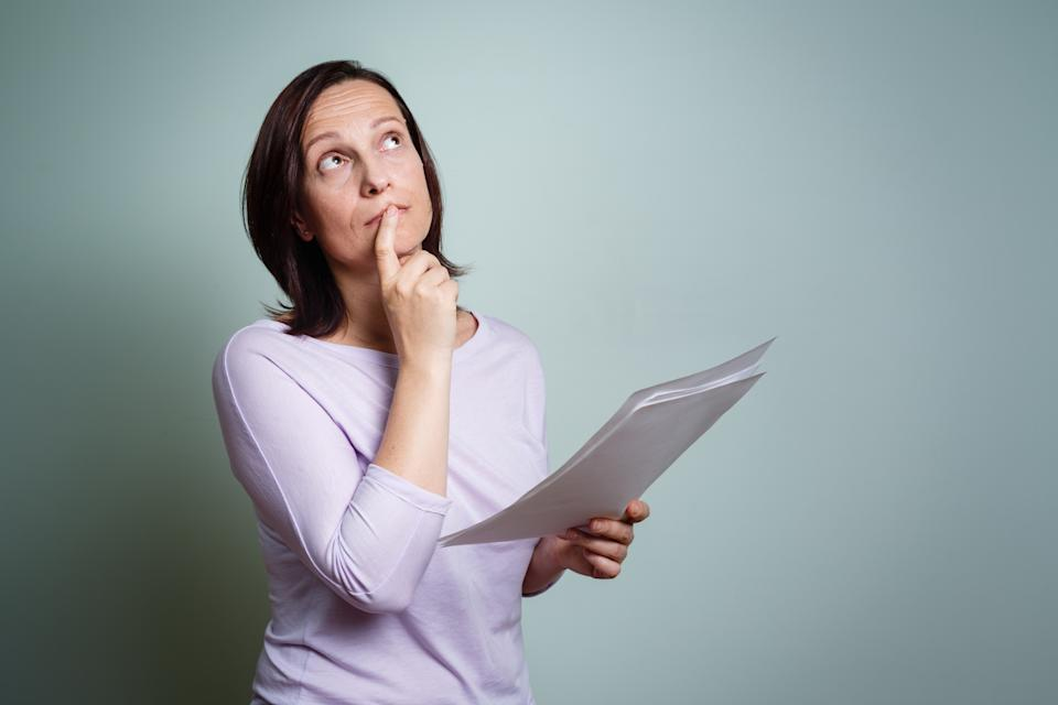 A woman holding paper sheets, looking up and thinking, possibly about lotto numbers.