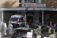 Paramedics and ambulances stand outside the first aid department of the Cotugno hospital in Naples, Italy, Friday, Nov. 13, 2020. The pandemic has heightened the urgency of the plight of those seeking medical care in public hospitals in Italy's economically under-developed south.(AP Photo/Gregorio Borgia)