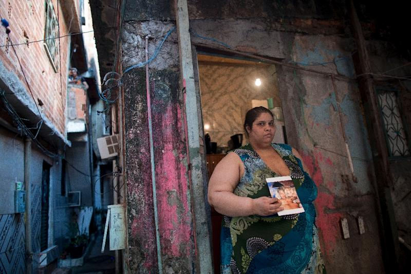Homemaker Kelly Cristina Pereira da Silva, whose son was killed by stray bullets, poses with her son's photo outside her house in the Manguinhos favela or shantytown in Rio de Janeiro, Brazil, on October 10, 2017