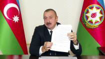 In this handout photo provided Tuesday, Nov. 10, 2020, by the Azerbaijan's Presidential Press Office, showing Azerbaijani President Ilham Aliyev gestures as he shows an agreement while addressing the nation in Baku, Azerbaijan. Armenia and Azerbaijan announced an agreement early Tuesday to halt fighting over the Nagorno-Karabakh region of Azerbaijan under a pact signed with Russia that calls for deployment of nearly 2,000 Russian peacekeepers and territorial concessions. (Azerbaijani Presidential Press Office via AP)