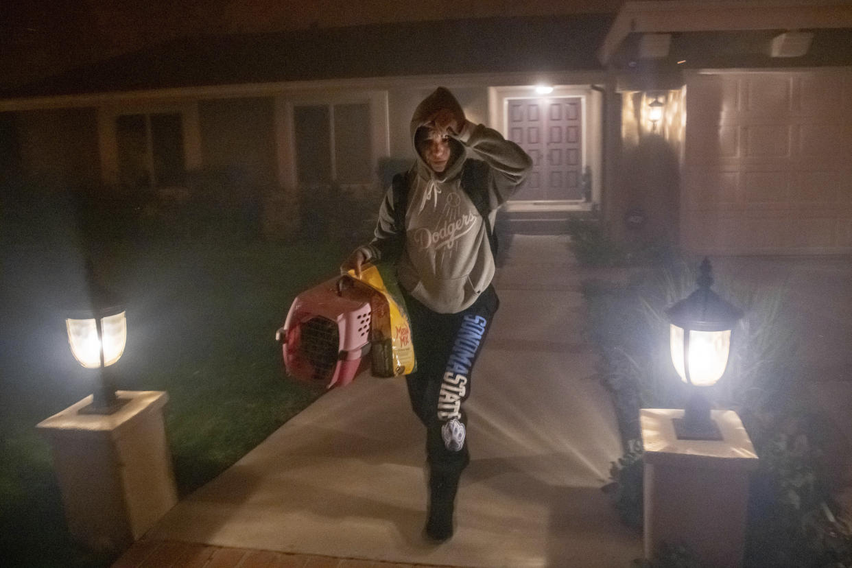 A woman evacuates her home with her cat as the Saddleridge fire threatens homes in Granada Hills, Calif., Friday, Oct. 11, 2019. (Photo: Michael Owen Baker/AP)